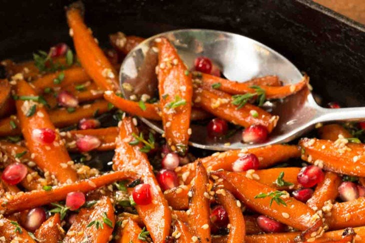 A gorgeous serving dish filled with sliced carrots, tossed in with pomegranate arils and fresh herbs.