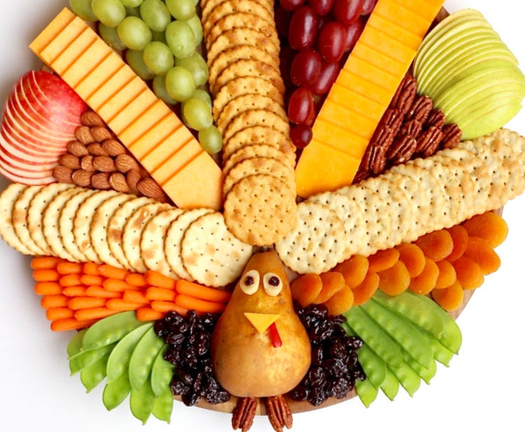 A cheese, fruit, and cracker platter that resembles a turkey