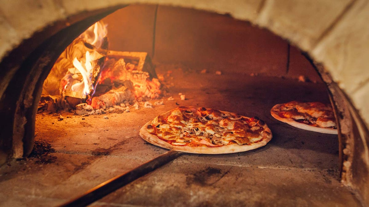 a pizza baking in a traditional wood-fired brick pizza oven