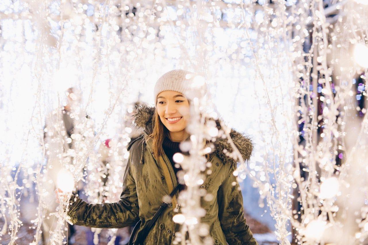 Woman walking through a Christmas light maze at Enchant Christmas