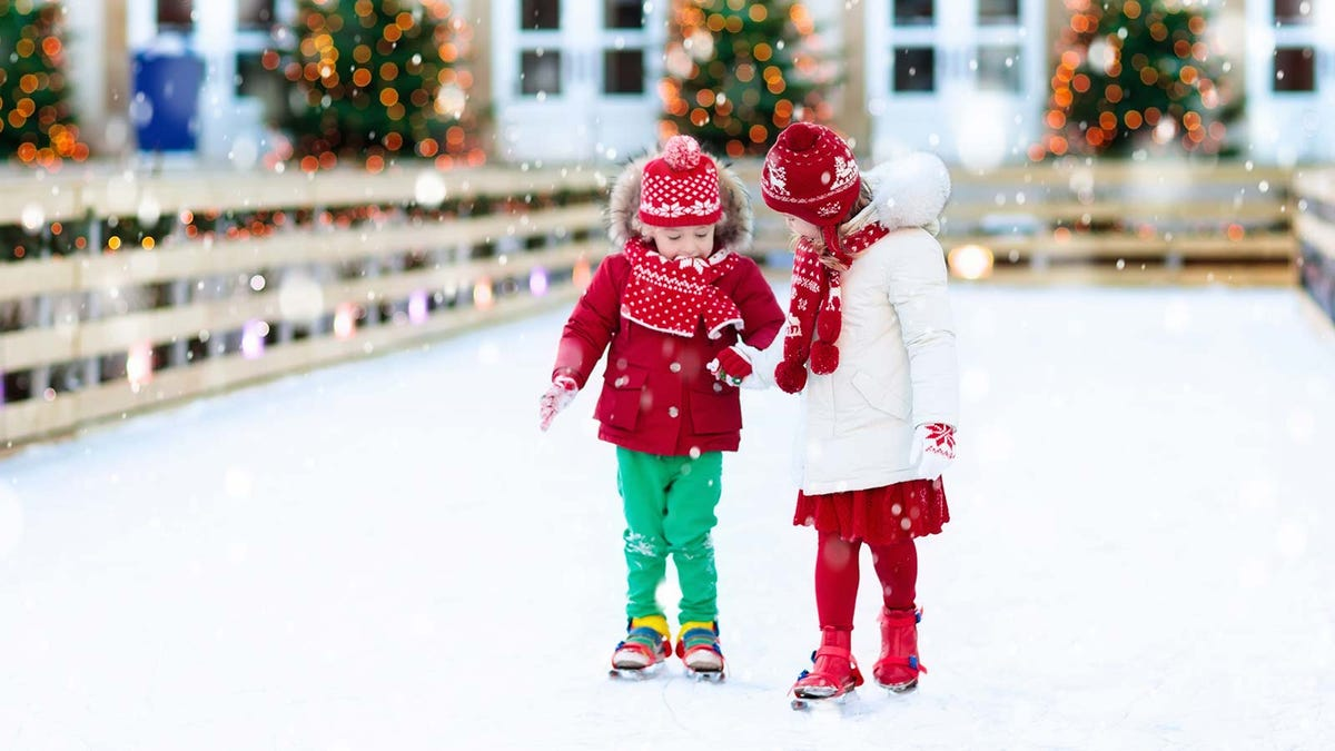 two children ice skating in a city skating rink