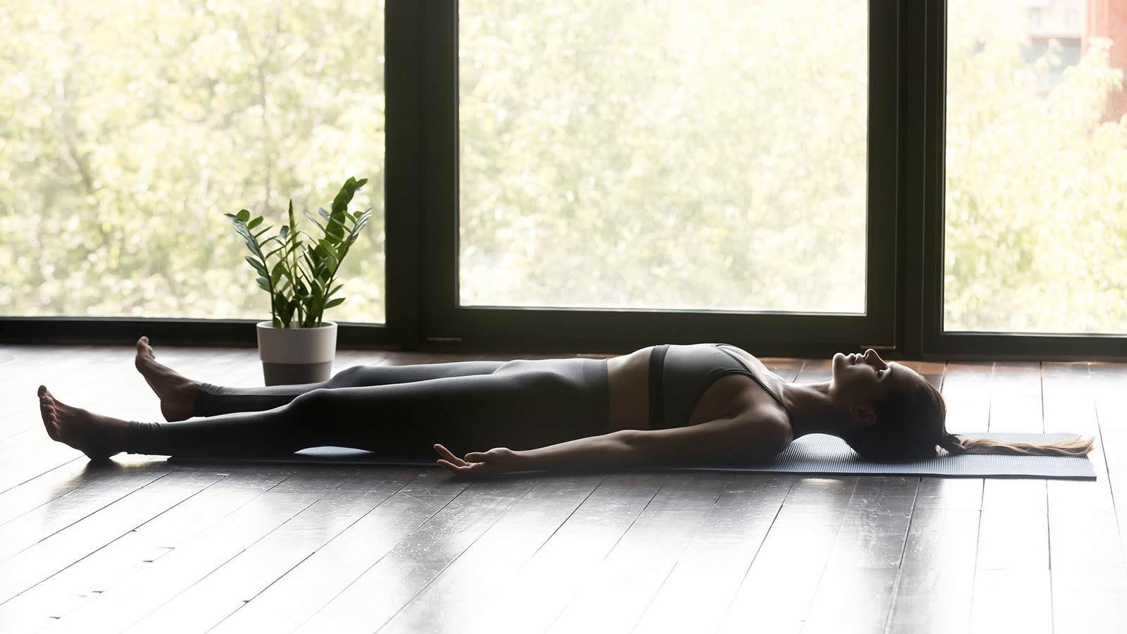 woman laying in savasana pose