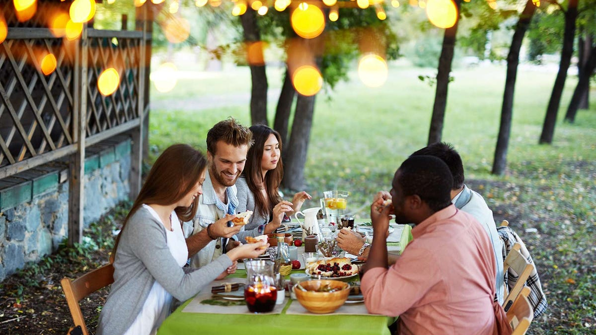 A group of people eating a meal at an outdoor table.