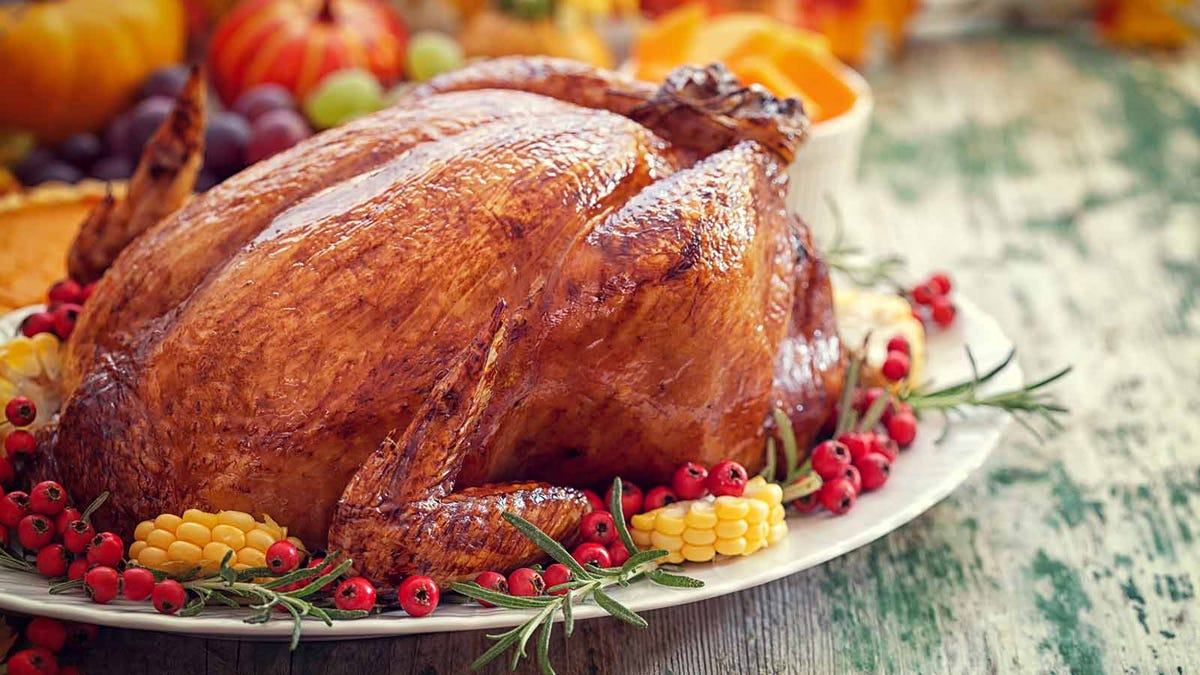 a delicious perfectly roasted turkey set out on a white serving platter