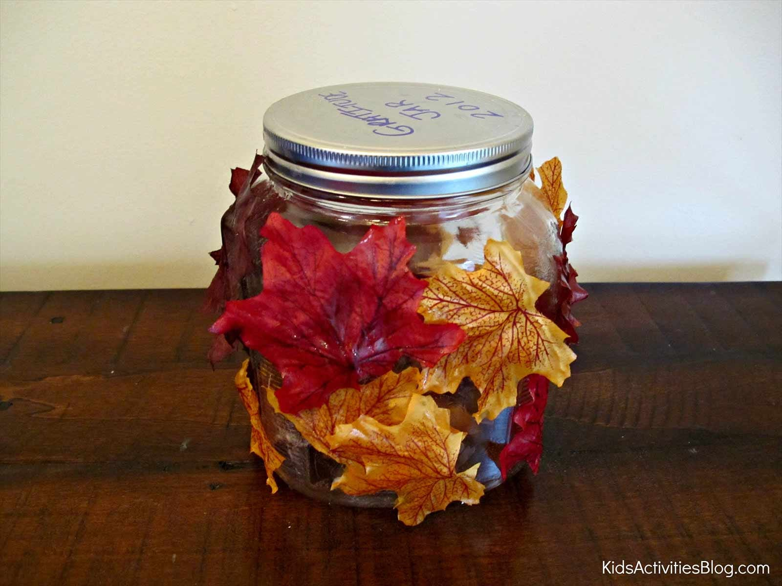 a glass jar decorated for Thanksgiving to hold gratitude notes