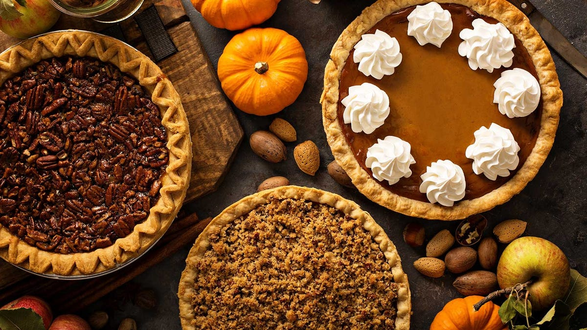 A holiday table set with many different kinds of pies.