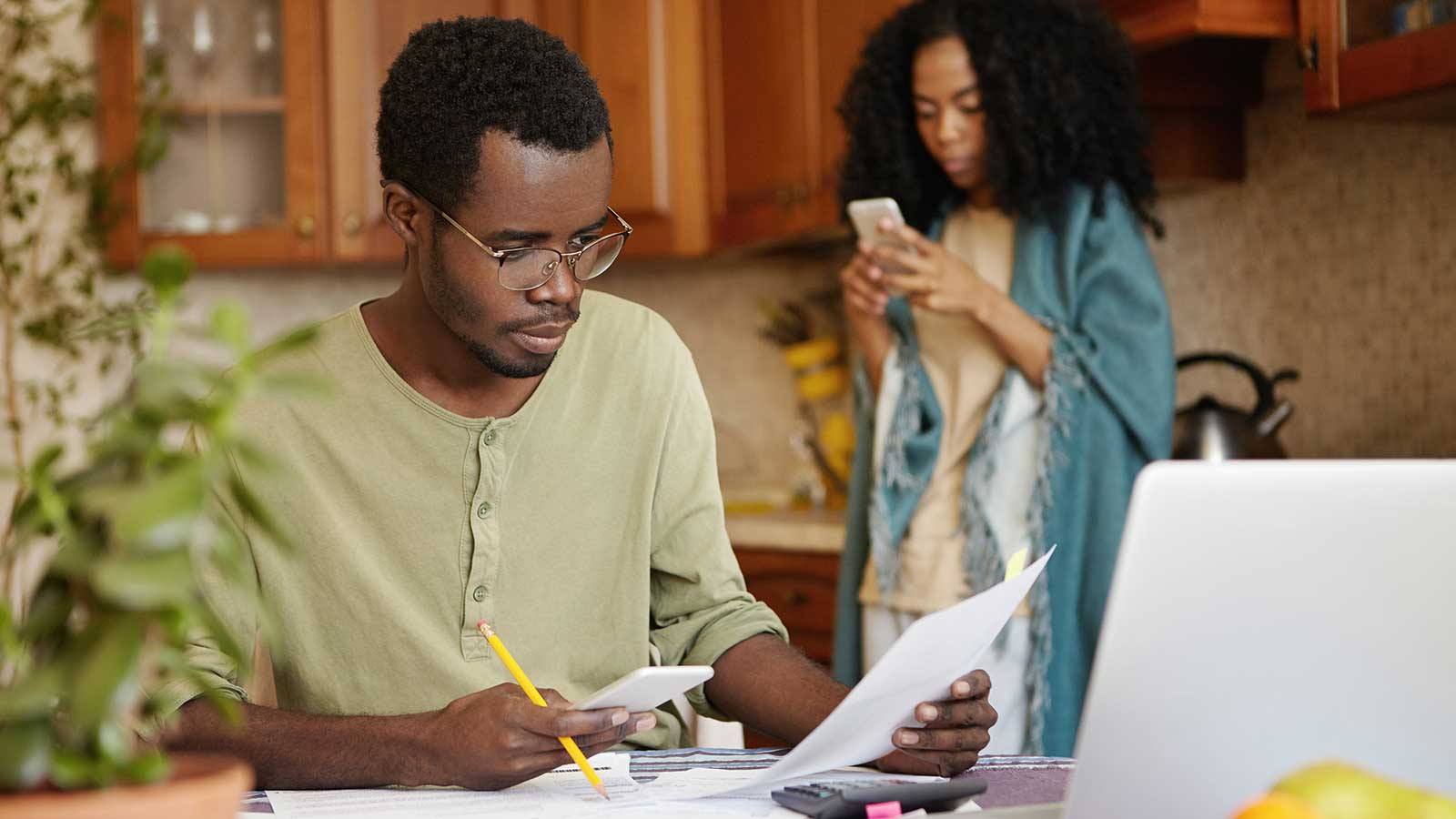 A man sitting at a kitchen table looking at a piece of paper, and holding a pencil and smartphone, and a woman in the background in pajamas looking at her phone.