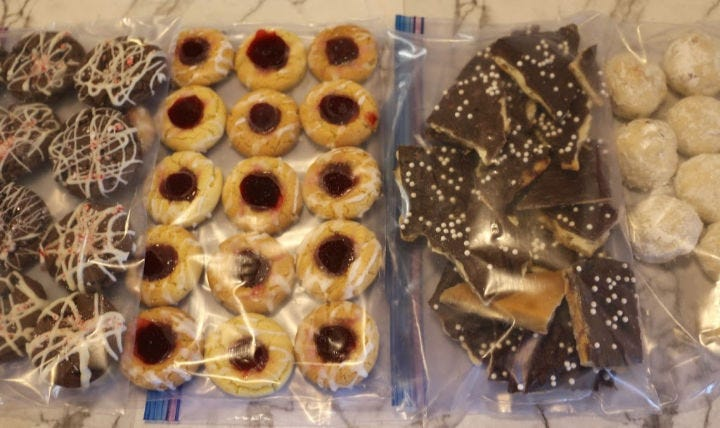 A batch each of chocolate fudge cookies, lemon raspberry cookies, Christmas crack, and snowballs in freezer bags.
