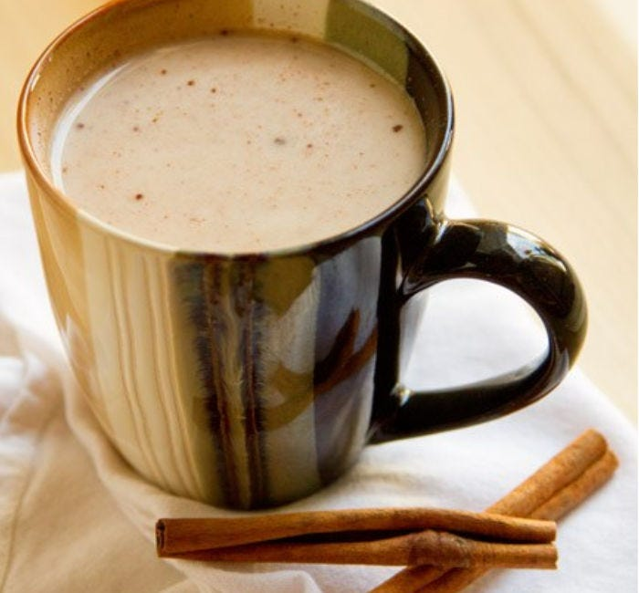 A mug filled with cinnamon hot tea, and two cinnamon sticks lying next to it.