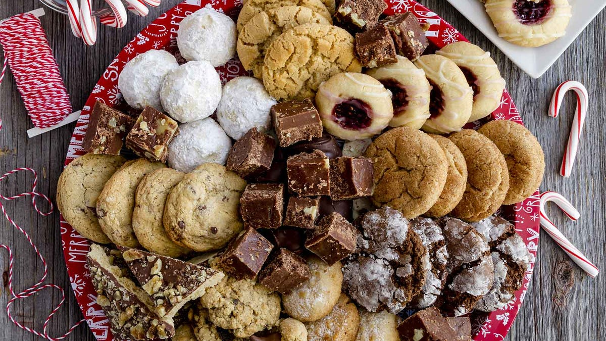 A platter full of various cookies and brownies surrounded by scattered candy canes.