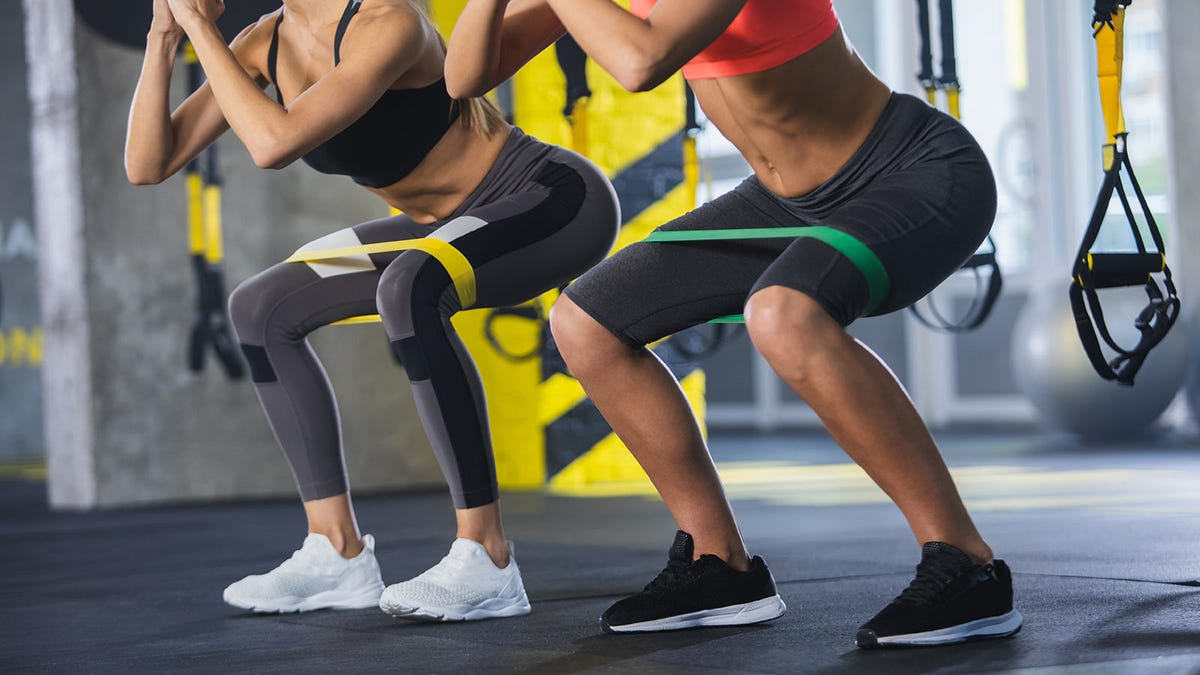Two women's legs as they do squats in a gym.