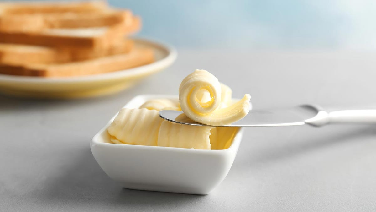 A butter dish with curls of butter on it.