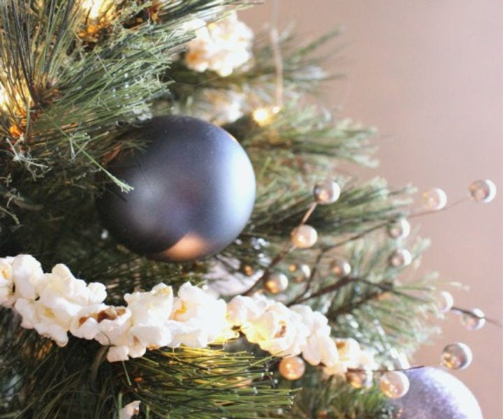 Handmade popcorn garland arranged on a Christmas tree with platinum silver ornaments and white lights.