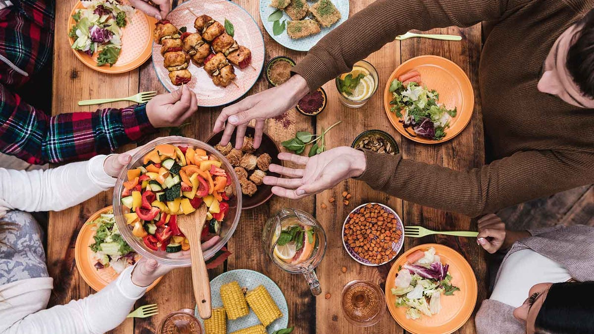 Friends sharing a meal with plenty of vegetarian options on the table.