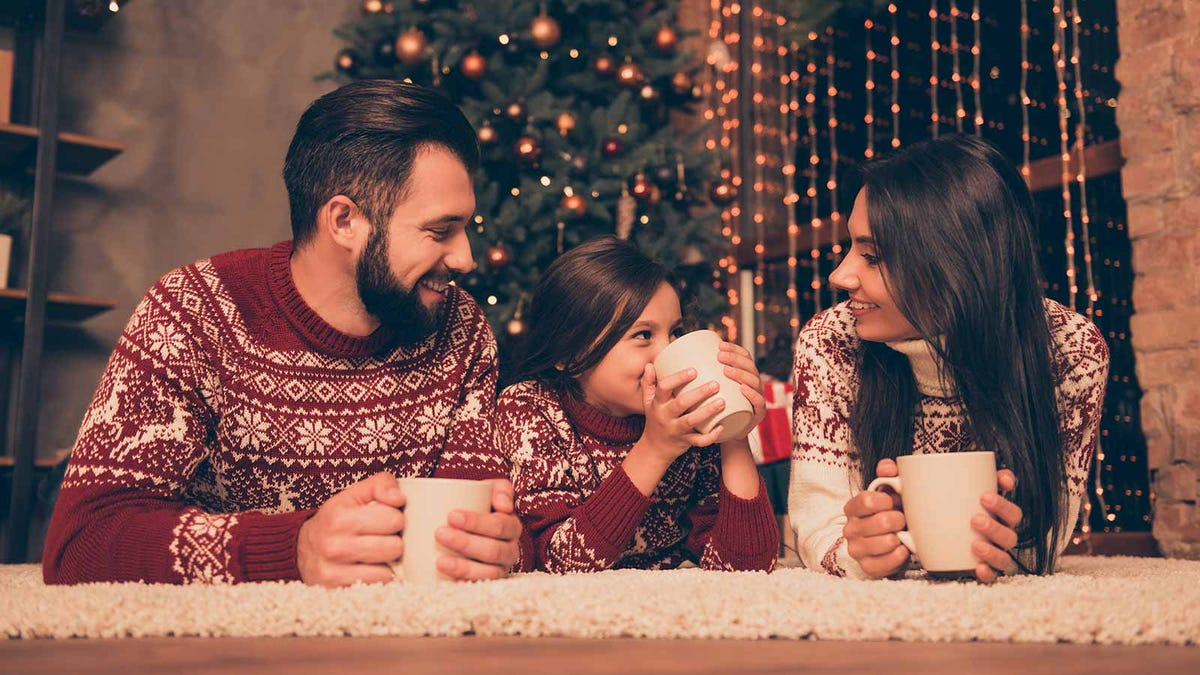 A Dad, Mom, and little girl lying on the floor by the Christmas tree drinking from mugs.