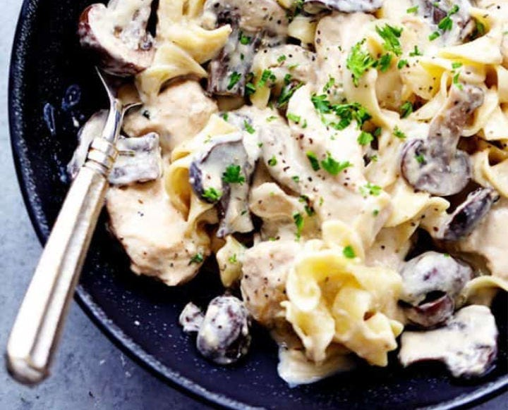 A black bowl filled with chicken and mushroom stroganoff.