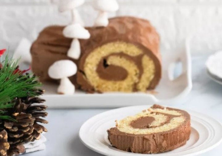 A slice of buche de noel cake with a full cake in the background. and decorative pinecones on the side.
