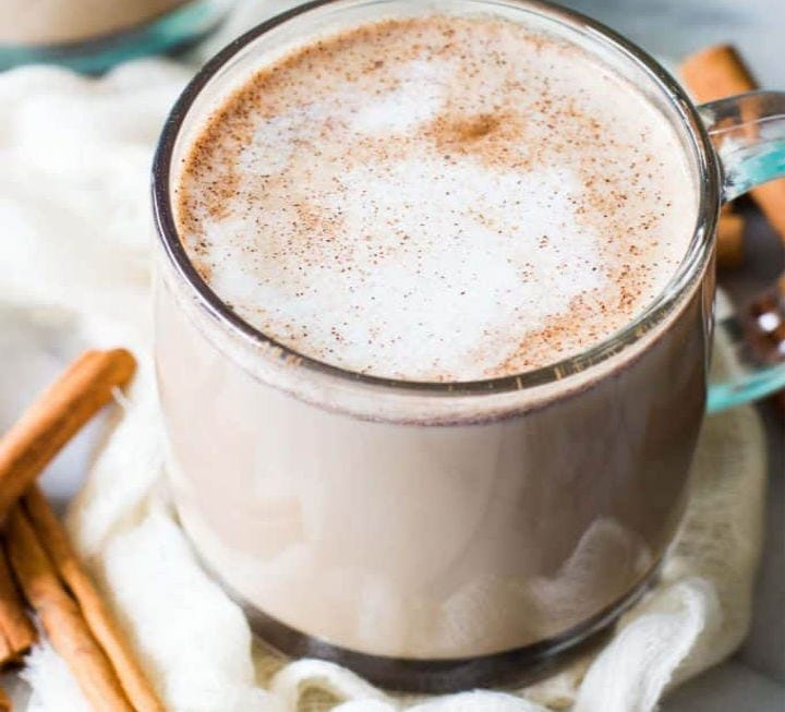 A mug full of Snickerdoodle Latte, and some cinnamon sticks lying next to it.