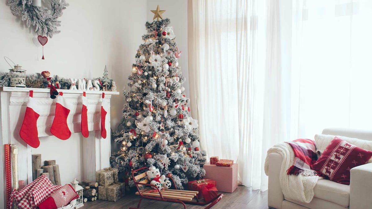 A beautifully decorated artificial tree in the corner of a brightly lit room.