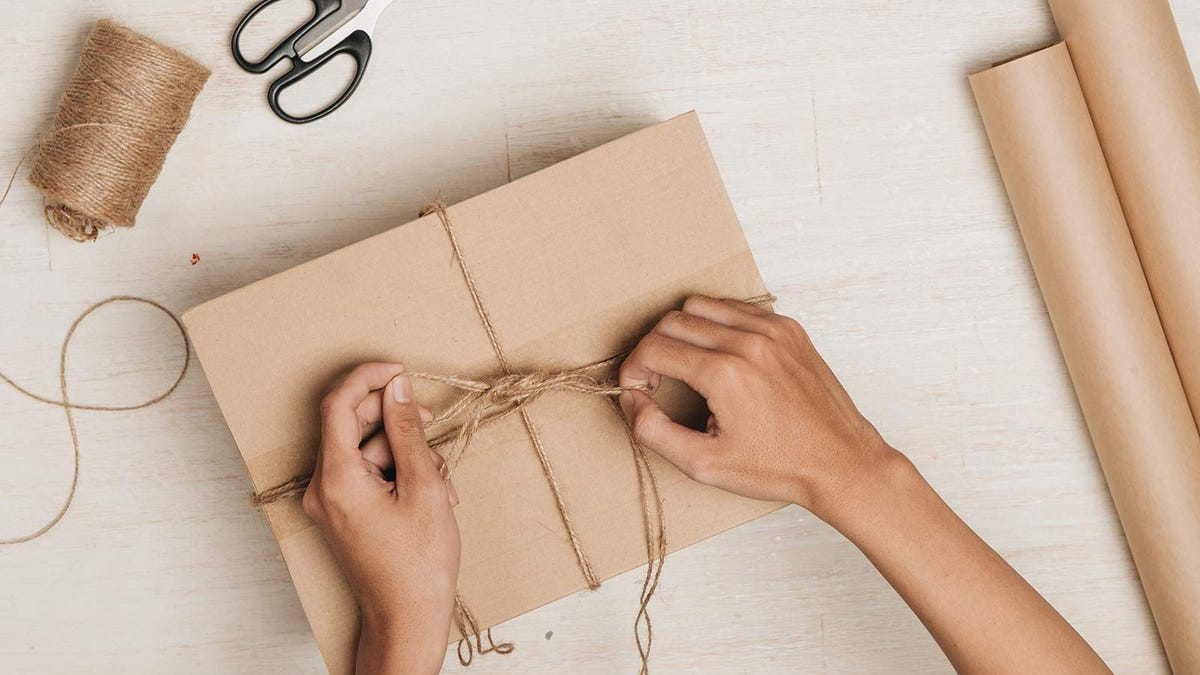 Someone tying up a package with twine