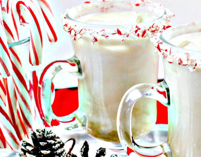 Two white glasses bar mugs filled with a peppermint white Russian, with a crushed candy cane rim.