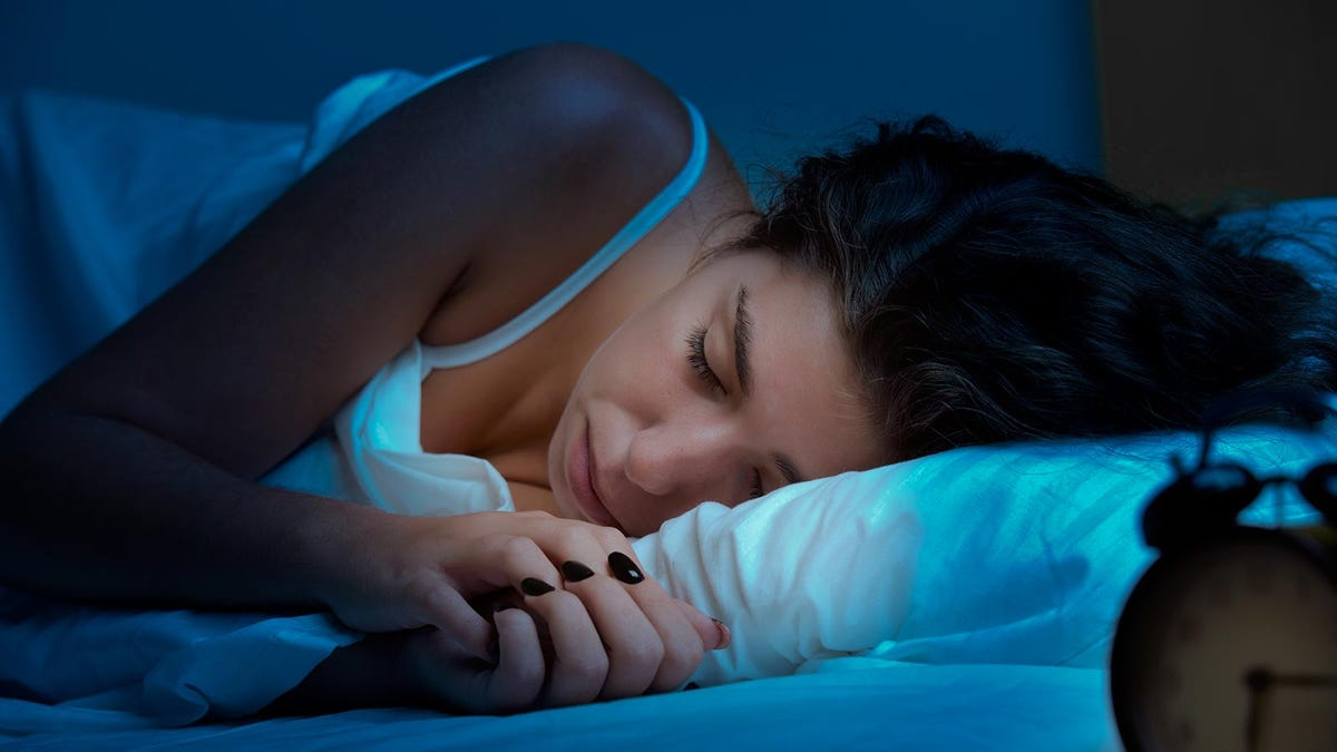 Woman sleeping in a dark and cool room.