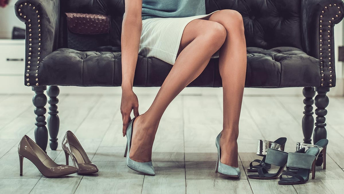 Woman trying on shoes in a boutique.