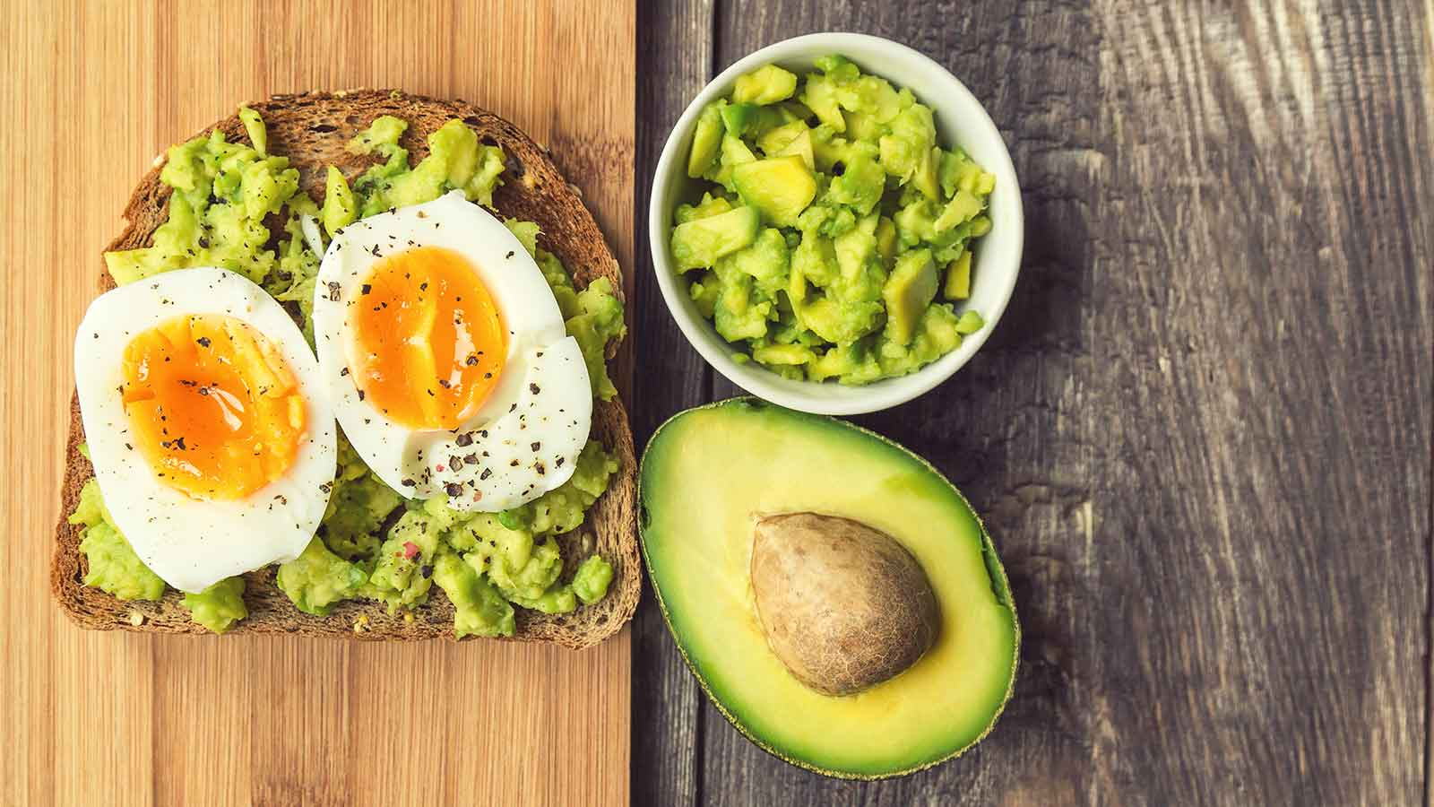 avocado with eggs on toast, sitting on a bamboo cutting board next to mashed up avocado