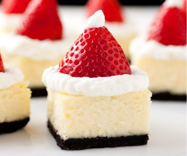 Small cheesecake bites decorated with strawberries and whipped cream to resemble Santa hats.