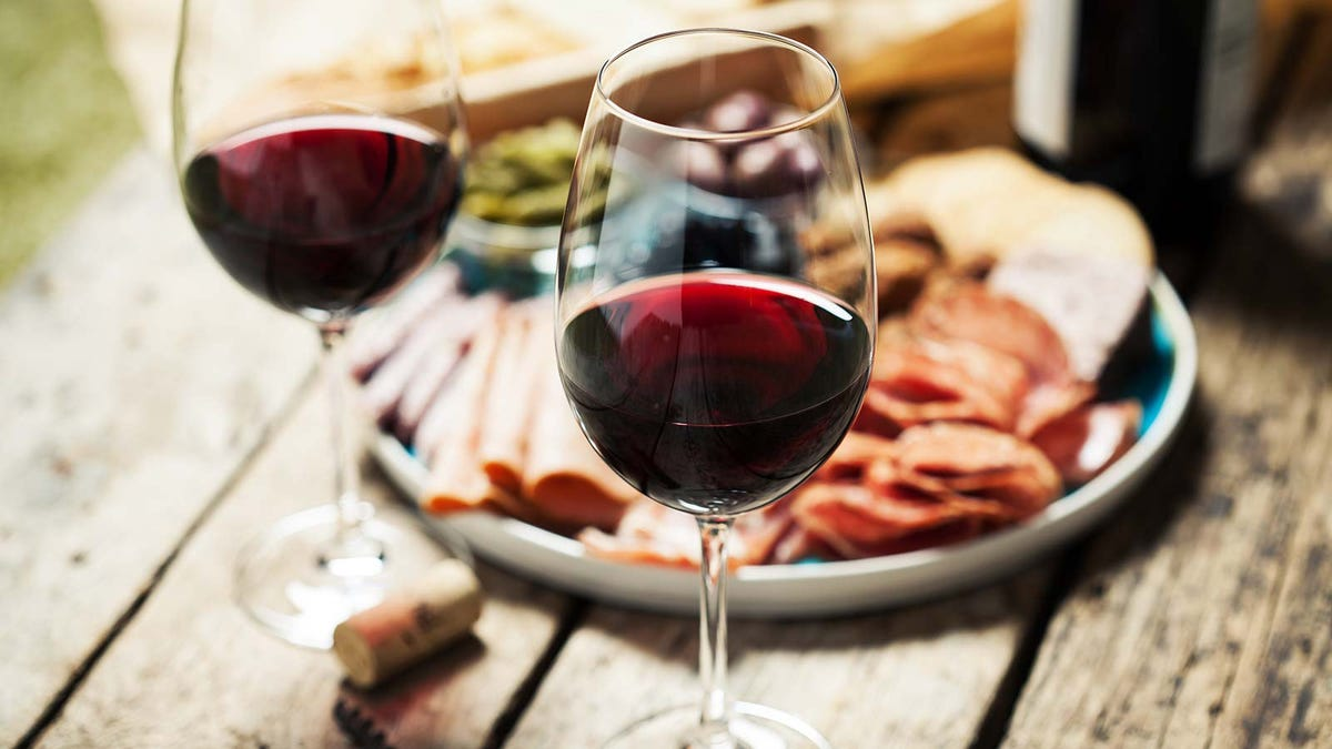 Two glasses of red wine on a rustic table in front of a charcuterie platter.