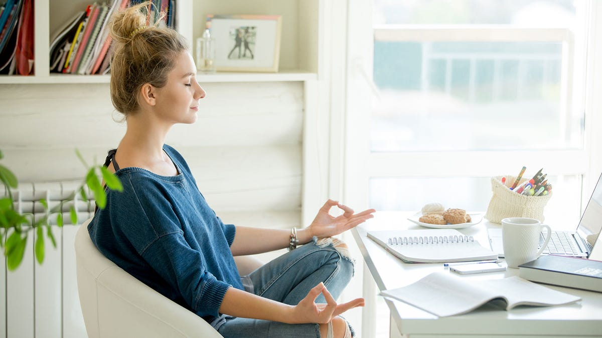 A woman meditating at her desk.