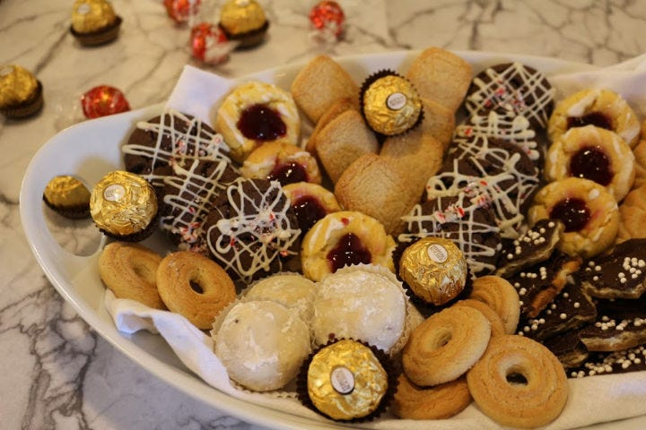 A white platter with various cookies arranged in clusters. .