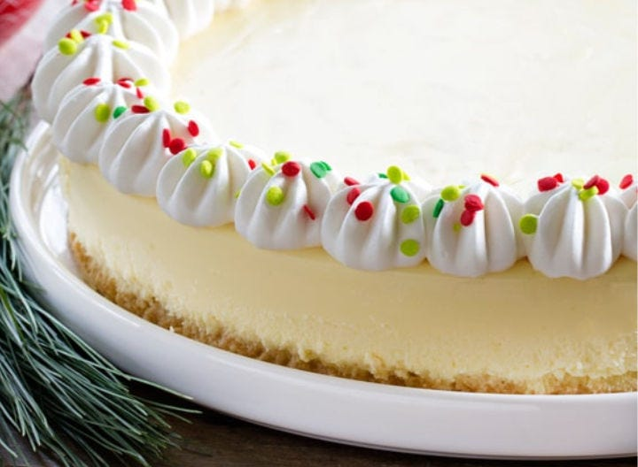 A full cheesecake with a piped boarder with festive sprinkles.