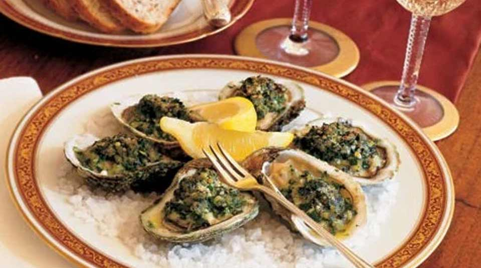 A plate of oysters Rockefeller on a table with gold stemware.