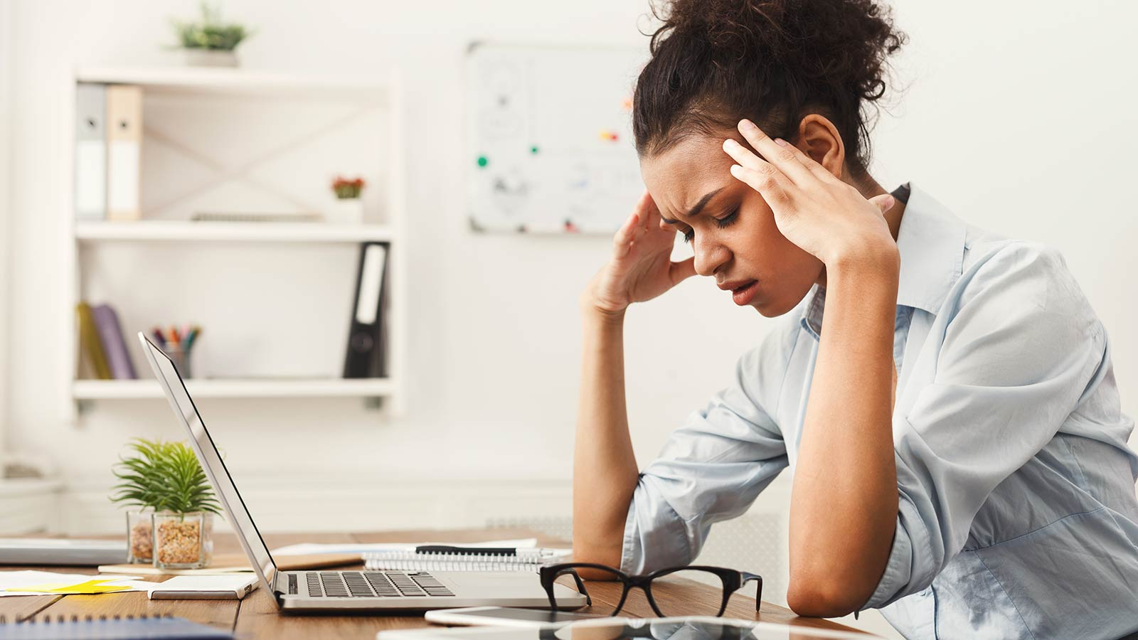 Woman rubbing her temples, overwhelmed by managing her productivity system.