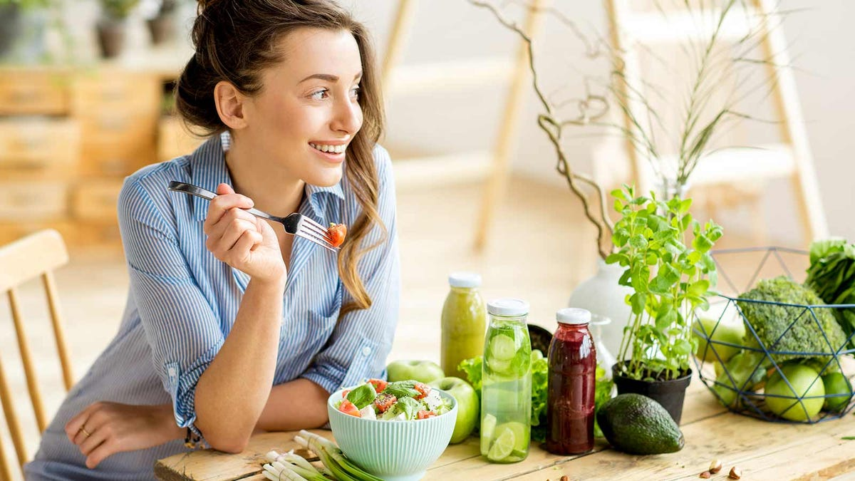 A woman sitting at a table eating a salad.