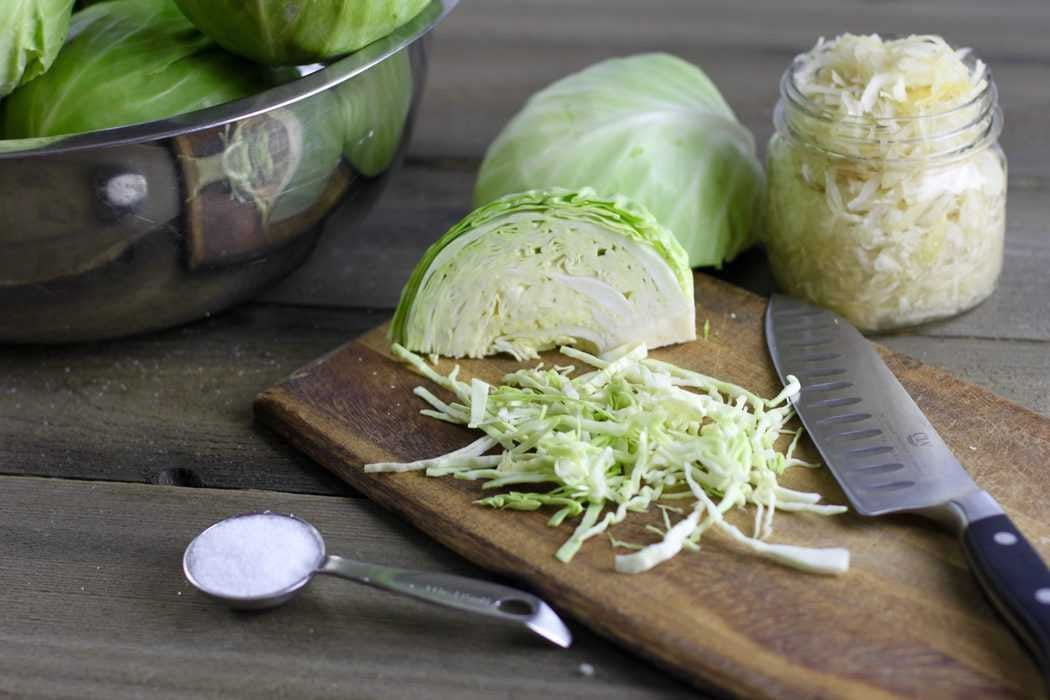 A cutting board with freshly chopped cabbage, salt, and a kraut starter.
