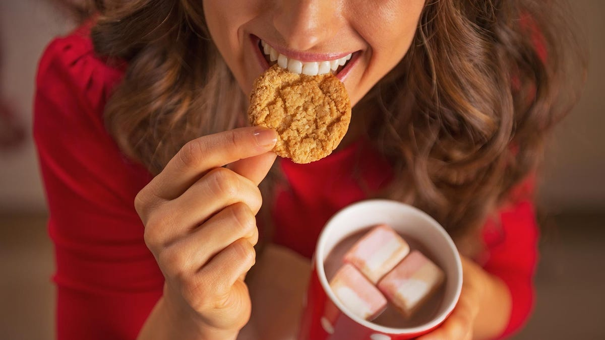 Woman eating a Christmas cookie while drinking some hot chocolate.