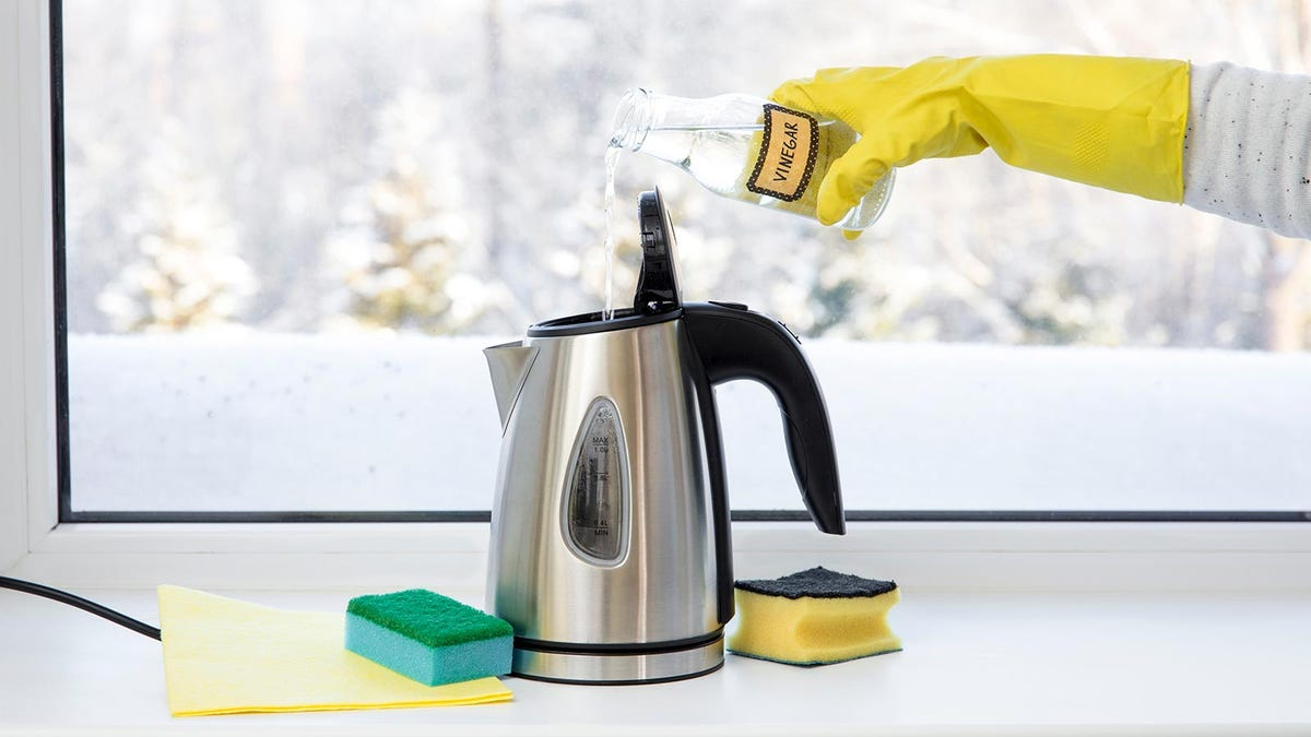 A hand wearing a yellow rubber glove pouring vinegar into an electric kettle.