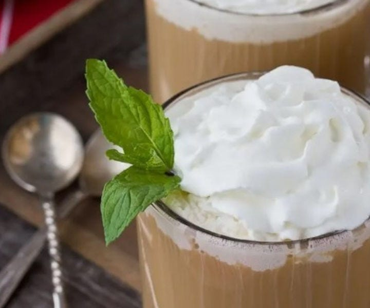 Two clear glasses filled with coffee toddy drink, garnished with whipped cream and a mint leaf with two spoons in the background.