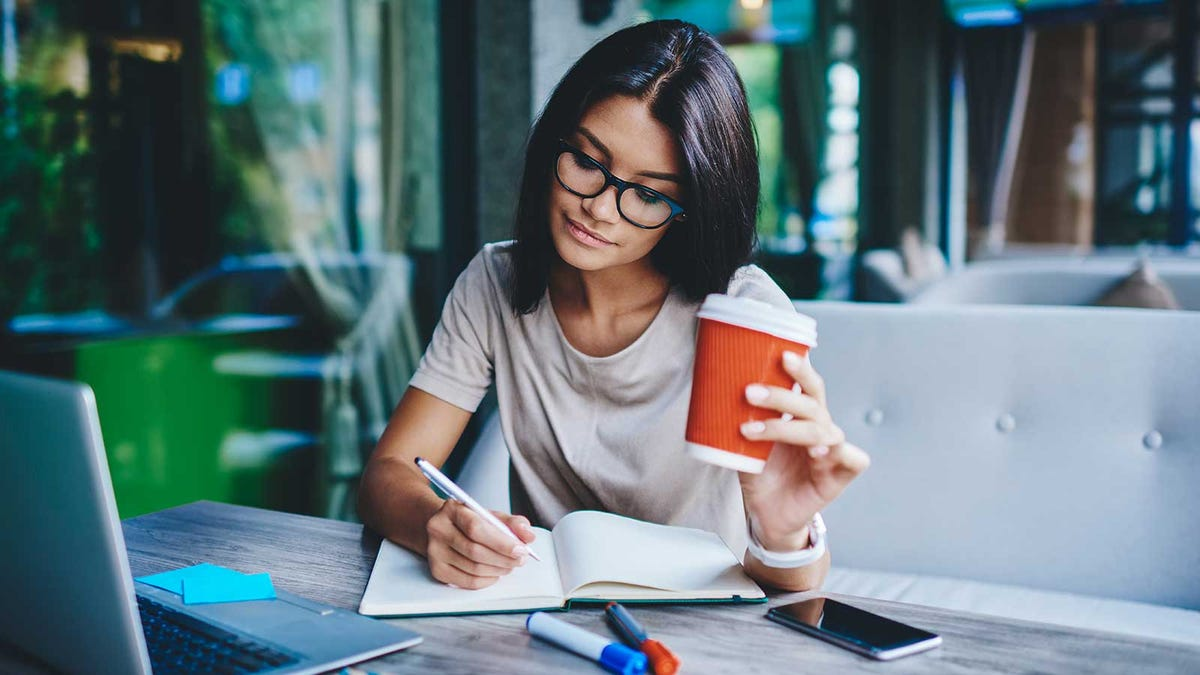 A woman sitting at a table with her laptop open, holding a cup of a coffee, and writing in a notebook.
