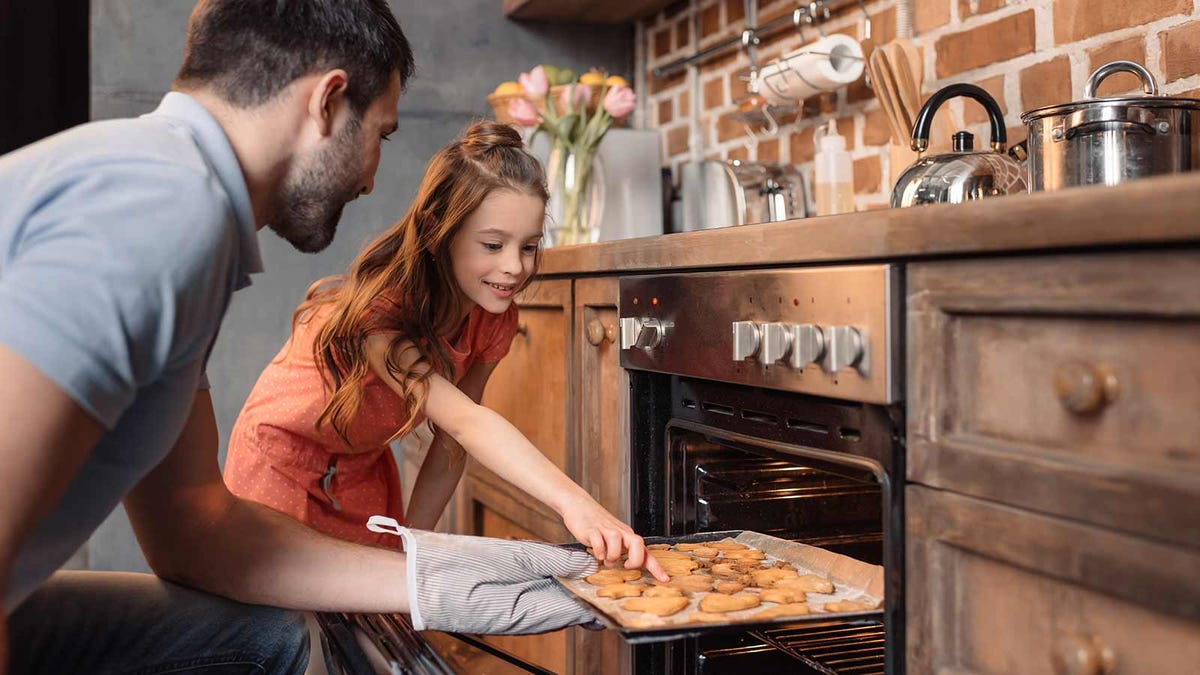 A dad and daughter pulling cookies out of the oven.
