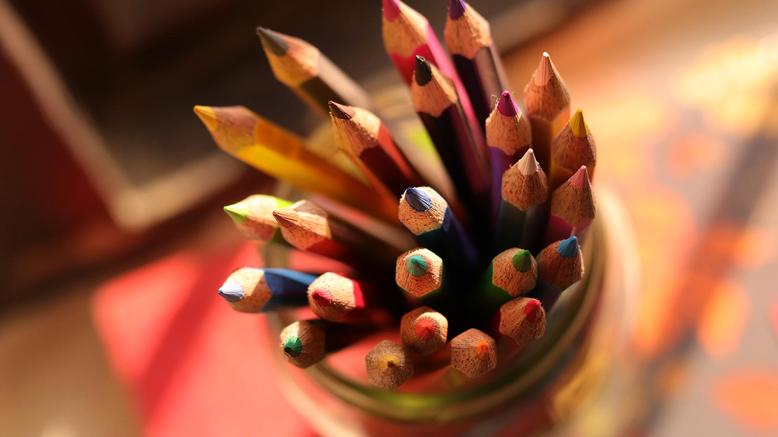 A mason jar filled with colored pencils.
