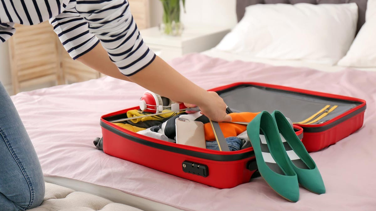 Woman unpacking suitcase after laying it on her bed.