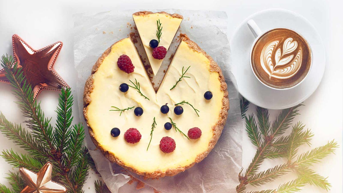 A delicious holiday cheese cake surrounded by pine branches and a cup of espresso with latte art.
