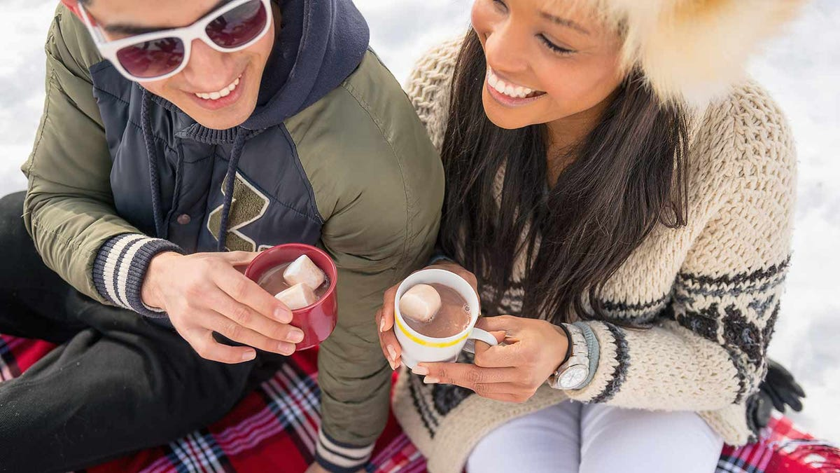 Two friends sharing some spiked hot chocolate on a cold.