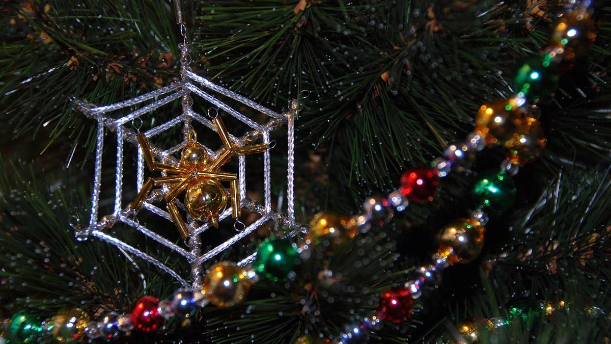 A spider Christmas ornament on a Christmas tree with garland.