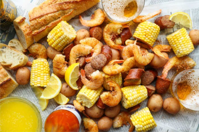 Shrimp boil placed on newspaper with a few cold beers and melted butter on the side.