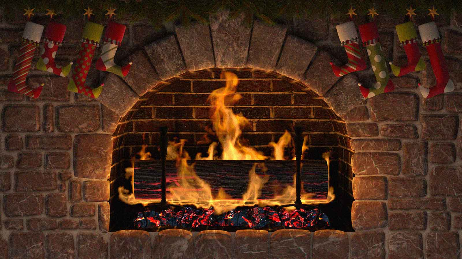 A yule log burning in a brick fireplace with stockings hung from the mantle.