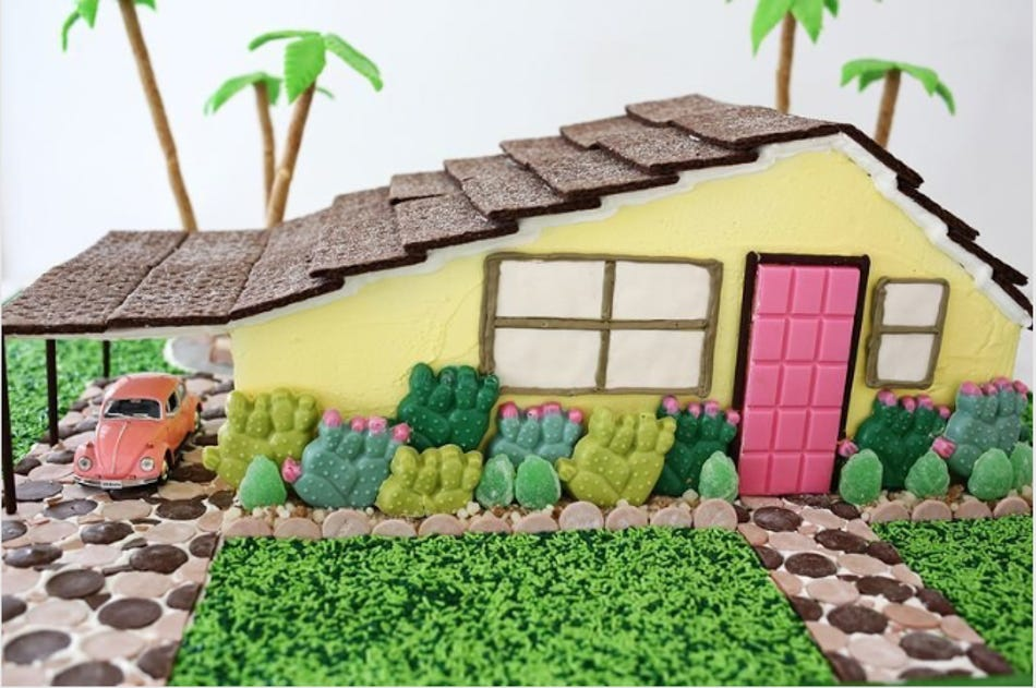A gingerbread candy bungalow with palm trees.